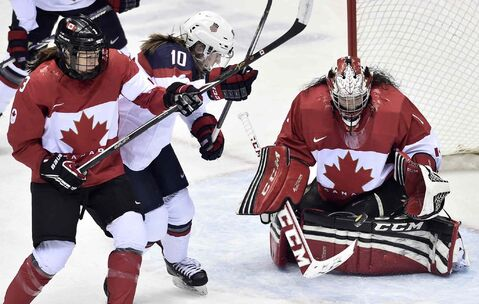 Goalie Shannon Szabados makes a save as teammate Jocelyne Larocque (left) ties up United States' Meghan Duggan during the first period in Sochi, Russia.