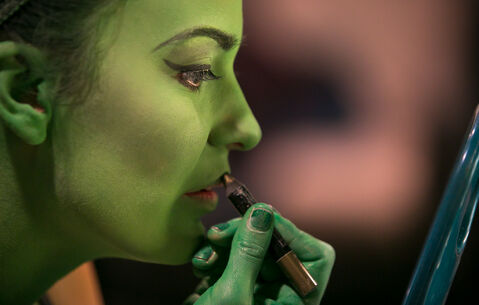 Alyssa Fox applies lipstick before a matinee show August 21st, after her green makeup was painted on for the part of Elphaba in the musical Wicked. The makeup process that turns Fox, an Elphaba standby, into the Wicked Witch of the West takes about 30 minutes. Makeup artist Joyce McGilberry applies a water-based green pancake makeup, and finishes with powder so green won't transfer to clothes or other performers. Wicked runs at the Centennial Concert Hall until August 30th. (Melissa Tait / Winnipeg Free Press)