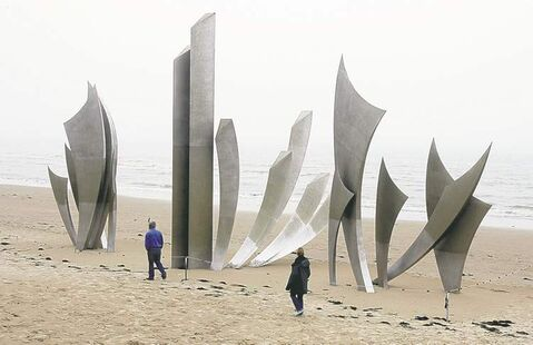 Visitors look at the sculpture The Braves at Omaha Beach in memory of soldiers who died.