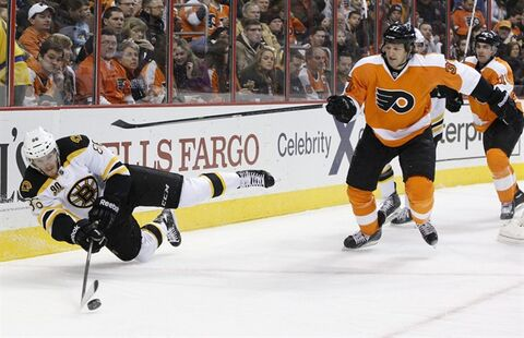 Boston Bruins' Kevan Miller, left, looks to pass the puck while falling as Philadelphia Flyers' Jay Rosehill, right, skates in during the second period of an NHL hockey game, Saturday, Jan. 25, 2014, in Philadelphia. (AP Photo/Chris Szagola)
