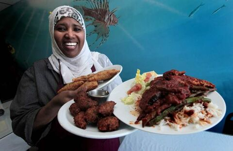 Roda Guled, owner of Sa'adal Kheyr restraunt with an armful of North Somali delecacies: samosas, falafel, and salmon with ochra.