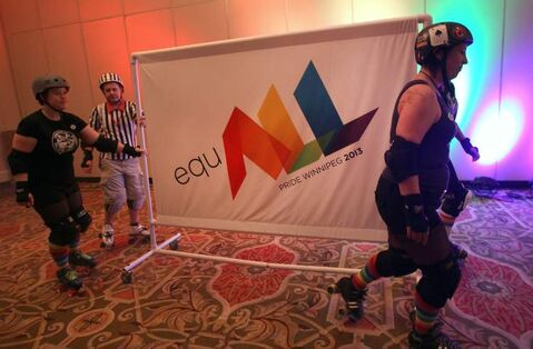 The new Pride banner is rolled in via roller girls at the Pride 2013 launch Thursday at the Delta Hotel.