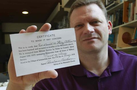 Korey Dyck, Director of the Mennonite Heritage Centre with a photocopy of Rev. David M. Stoesz's First World War exemption card. (The original card is at the Canadian War Museum.)