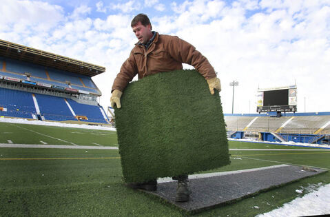 Todd Leathwood cuts pieces of the turf at the Canad Inns Stadium that will become part of framed memory collections. Everything at the stadium that hasn't been claimed yet is for sale.