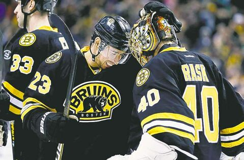Boston Bruins' Chris Kelly (23) celebrates with teammate Tuukka Rask (40), of Finland, after the Bruins defeated the Winnipeg Jets 2-1 in a shootout during an NHL hockey game in Boston, Monday, Jan. 21, 2013. (AP Photo/Michael Dwyer)