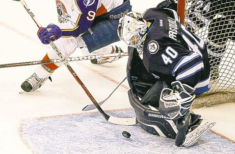 St. John's IceCaps goalie,Eddie Pasquale (right) blocks a shot.