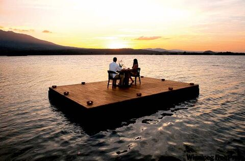 A couple enjoys a candlelight dinner on a floating deck at Jicaro Lodge on Lake Nicaragua.