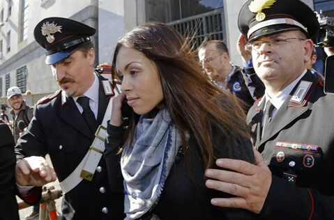 Karima el-Mahroug's is escorted outside the Milan's Law court by two Carabinieri police officers after giving her testimony at the trial of three former Berlusconi aides accused with procuring her and other woman for prostitution, in Milan, Italy, Friday, May 17, 2013. Silvio Berlusconi's private disco featured not only aspiring show girls performing striptease acts as sexy nuns and nurses, but also dressed as President Barack Obama and a prominent Milan prosecutor whom the billionaire media mogul has accused of persecuting him, according to the first public sworn testimony by the Moroccan woman at the center of the scandal. (AP Photo/Luca Bruno)