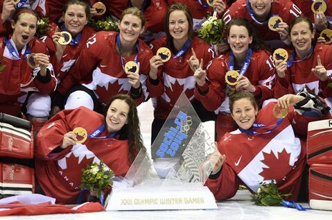 Team Canada poses for a team photograph with their gold medals after defeating Team USA in overtime to win the women's gold medal hockey game at the Sochi Winter Olympics Friday February 21, 2014 in Sochi, Russia. THE CANADIAN PRESS/Paul Chiasson