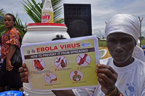 A Liberian woman holds up a pamphlet with guidance on how to prevent the Ebola virus from spreading, in the city of Monrovia, Liberia, Thursday, Aug. 14, 2014. Liberian officials faced a difficult choice Thursday: deciding which handful of Ebola patients will receive an experimental drug that could prove life-saving, ineffective or even harmful. (AP Photo/Abbas Dulleh)
