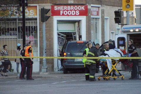 Emergency personnel move a person into an ambulance after a collision at Ellice Avenue and Sherbrook Street early Tuesday morning.