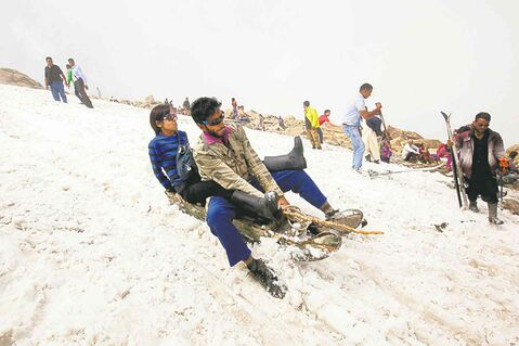 Indian tourists enjoy sledge ride in snow in Afarwat.