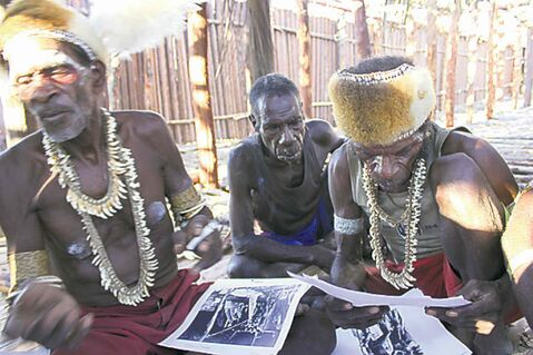 Asmat men look at photos taken by Michael Rockefeller.