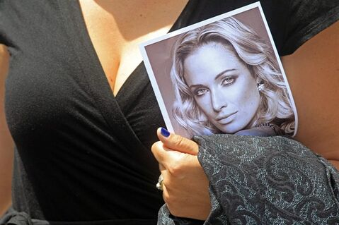 File - In this Feb. 19, 2013, file photo, a woman holds a photo of Reeva Steenkamp, as she leaves her funeral, in Port Elizabeth, South Africa. Oscar Pistorius' murder trial will have a dedicated 24-hour television channel in South Africa, the country's top cable provider said, Wednesday, Jan. 29, 2014, promising