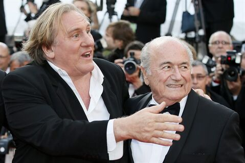 FIFA President Sepp Blatter, right, and actor Gerard Depardieu pose for photographers as they arrive for the screening of The Homesman at the 67th international film festival, Cannes, southern France, Sunday, May 18, 2014. (AP Photo/Alastair Grant)