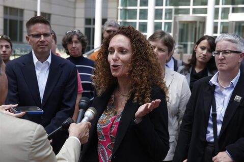 Attorney Mari Newman, center, talks with members of the media, as she stands with her plaintiffs and their supporters following a court hearing on sam sex marriage at the Federal District Court, in Denver, Tuesday, July 22, 2014. Gay couples seeking to strike Colorado's same-sex marriage ban urged a federal judge Tuesday to overturn the law immediately and reject the state's request to stay a ruling until the U.S. Supreme Court decides the matter. (AP Photo/Brennan Linsley)