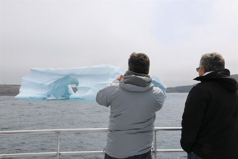 Jean-Pierre Renaud (left) of Laval, Que., and Charles Renaud of Blainville, Que. look at a iceberg off the coast of Cape Spear, N.L., on May 31, 2014. THE CANADIAN PRESS/Mike Wert