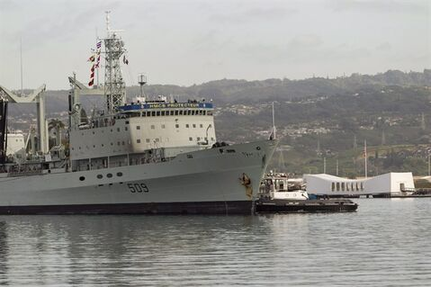 With the USS Arizona Memorial in the background, the Royal Canadian ship HMCS Protecteur is towed into Joint Base Pearl Harbor-Hickam Thursday, March 6, 2014 in Honolulu after suffering an engine fire aboard the ship while at sea. National Defence was warned a year before the devastating fire aboard HMCS Protecteur that the electrical system, main engine controls and navigation system aboard both of the navy's supply ships were on their last legs and prone to catastrophic failure. The unusually blunt assessment was contained in a four-page confidential briefing note prepared by the former head of the navy as he was about to retire last year. THE CANADIAN PRESS/AP-Marco Garcia