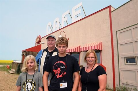 Aidan, Ben, Ian and Angela Garvie (left to right) pose in front of The Ruby Cafe on the set of Corner Gas in Rouleau, Sask., on Wednesday, July 16, 2014. The Californian family and Corner Gas fans gave money to the movie via a Kickstarter campaign and were rewarded with a day on the set during filming. THE CANADIAN PRESS/Michael Bell