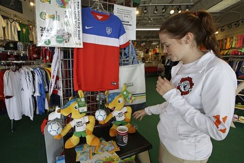 Employee Darcy Aders adjusts World Cup items that are for sale at Soccer Village, Wednesday, June 25, 2014, in Cincinnati. Excitement is high in the city with a rich German heritage for Thursday's World Cup match between the United States and Germany. (AP Photo/Al Behrman)