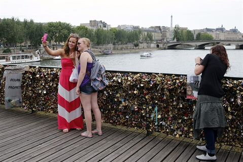 Tourists take selfies with their phone on the Pont des Arts bridge in Paris, Monday, June 9, 2014. The thousands of locks that cling like barnacles to the Pont des Arts in Paris have become a symbol of danger, rather than love, after a chunk of fencing fell off under their weight. The fencing tumbled late Sunday on the pedestrian bridge, which crosses the Seine. (AP Photo/Francois Mori)