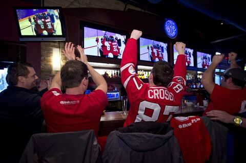 Fans react to Canada's 1-0 victory against the Americans on Friday, February 21, 2014 in a Levis Que. sports bar. THE CANADIAN PRESS/Jacques Boissinot