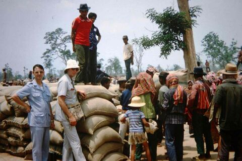 DeFehr (in white hat) next to rice seeds ready to be distributed in Cambodia in the late 1970s.