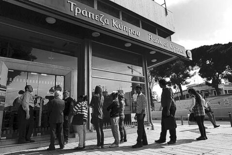 People wait in line to enter a branch of the Bank of Cyprus in Nicosia on March 28.