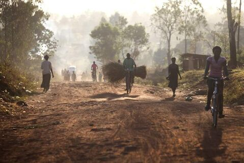 Ugandans start their day early, making their way down a dusty highway near the town of Gulu.