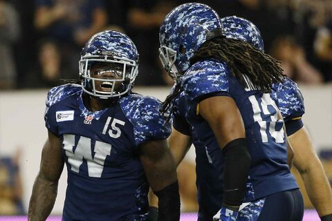 Winnipeg Blue Bombers' Troy Stoudermire (15) and Don Unamba (13) celebrate Stoudermire's punt return during the second half of CFL action in Winnipeg Friday, August 22, 2014.