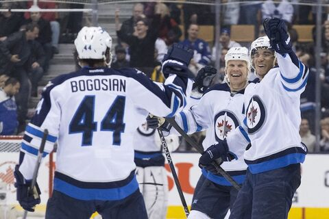 Winnipeg Jets' Evander Kane (right) and Olli Jokinen congratulate Zach Bogosian after he scored the winning goal in tenth round of the shootout in Saturday night's game against the Toronto Maple Leafs.