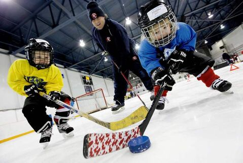 Mike Loustel, shown tutoring Brucen Muys (left) Joseph Brown at World 3-on-3 Hockey Federation, used to be a proponent of year-round hockey. Now he's an advocate of moderation.