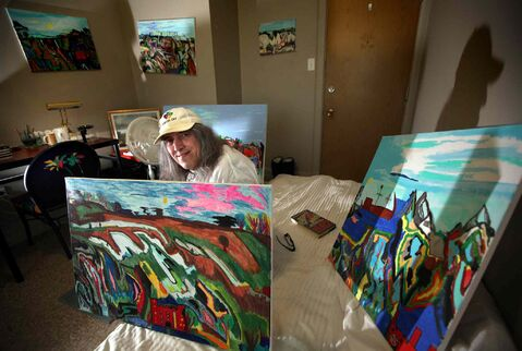 Wayne Bryant in his room with his paintings.