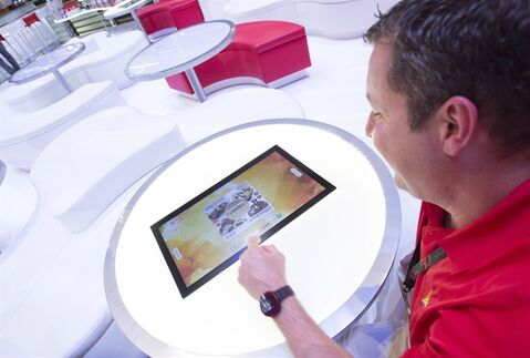 A man orders food and a coffee from a touch screen while seated at his table in a prototype of a Tim Hortons