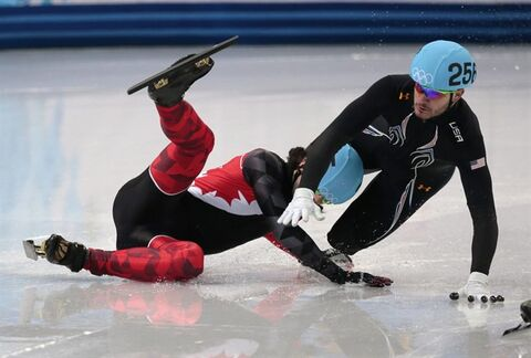 Eduardo Alvarez of the United States, right, and Charles Hamelin of Canada crash out in a men's 1000m short track speedskating quarterfinal at the Iceberg Skating Palace during the 2014 Winter Olympics, Saturday, Feb. 15, 2014, in Sochi, Russia. (AP Photo/Ivan Sekretarev)