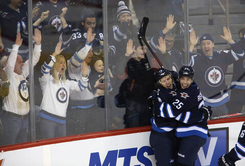 Winnipeg Jets' Bryan Little (18) and Zach Redmond (25) celebrate after the pair combined for Little's game winning goal against the Florida Panthers during NHL hockey action overtime action in Winnipeg.