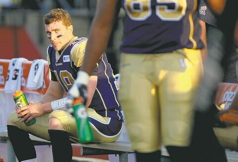 Winnipeg Blue Bombers quarterback Justin Goltz sits on the bench after throwing a 115 yard interception to end the second quarter of CFL pre-season action against the Hamilton Tiger-Cats in Guelph, Ontario Thursday, June 20, 2013. THE CANADIAN PRESS/Aaron Lynett