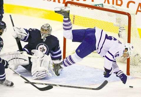 Toronto's Clarke MacArthur (right) flies through the air after colliding with Jets goaltender Ondrej Pavelec during the second period Thursday.