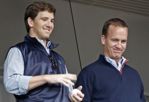 Denver Broncos quarterback Peyton Manning, right, and his brother, New York Giants quarterback Eli Manning, watch from New York Yankees' Derek Jeter's suite during a baseball game between the Yankees and the Tampa Bay Rays at Yankee Stadium in New York, Sunday, May 4, 2014. (AP Photo/Kathy Willens)