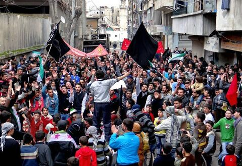 This citizen journalism image provided by Aleppo Media Center AMC which has been authenticated based on its contents and other AP reporting, shows anti-Syrian regime protesters holding banners and chanting slogans, during a demonstration in the neighborhood of Bustan Al-Qasr in Aleppo, Syria, Friday, March. 1, 2013. Syrian government forces fought fierce clashes with rebels attacking a police academy near the northern city of Aleppo on Friday, while the bodies of 10 men most of them shot in the head were found dumped along the side of a road outside Damascus, activists said. (AP Photo/Aleppo Media Center AMC)
