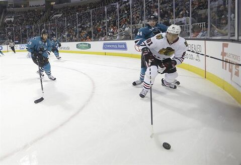 Chicago Blackhawks right wing Marian Hossa (81), of the Czech Republic, skates past San Jose Sharks defenseman Marc-Edouard Vlasic (44) and Joe Thornton (19) during the second period of an NHL hockey game in San Jose, Calif., Saturday, Feb. 1, 2014. (AP Photo/Tony Avelar)