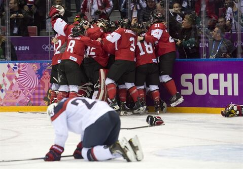 USA's Michelle Picard kneels on the ice as Canada celebrates their overtime win in the gold medal hockey game at the Sochi Winter Olympics Thursday February 20, 2014 in Sochi, Russia. Canada's men will play the United States in semi-final action Friday. THE CANADIAN PRESS/Adrian Wyld