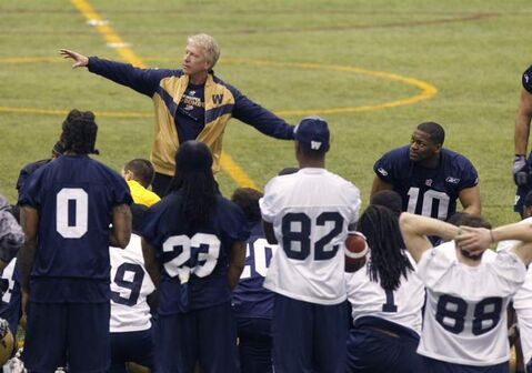 Winnipeg Blue Bombers head coach Tim Burke talks to players, including slotback Terrence Edwards (82), Wednesday during the first day of the team's three-day mini-camp held at the Winnipeg Indoor Soccer Complex.