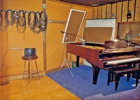 The piano and control-room window in the studio.