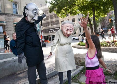 Promoting their show, Grim and Fischer, Andrew Phoenix (left) and Kate Braidwood (centre) interact with Destiny Lavallee (right) at the Old Market Square.
