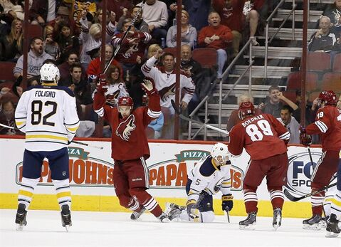 Phoenix Coyotes' Antoine Vermette, second from left, celebrates his goal as Buffalo Sabres' Chad Ruhwedel (5) looks for the puck and Sabres' Marcus Foligno (82) and Coyotes' Mikkel Boedker (89), of Denmark, and Shane Doan (19) look on during the first period of an NHL hockey game on Thursday, Jan. 30, 2014, in Glendale, Ariz. (AP Photo)