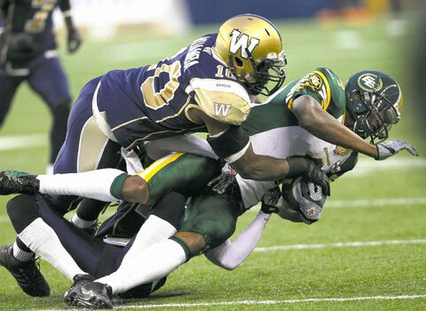 The Bombers' Henoc Muamba tackles the Eskimos' Adarius Bowman during first-half play Friday at Investors Group Field.