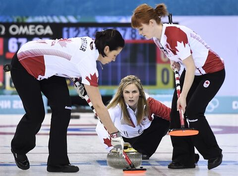 Canada skip Jennifer Jones centre, throws her rock as second Jill Officer, left, and lead Dawn McEwen, right, sweep while playing against China in the first end during the 2014 Sochi Winter Olympics in Sochi, Russia on Monday, February 10, 2014. THE CANADIAN PRESS/Nathan Denette