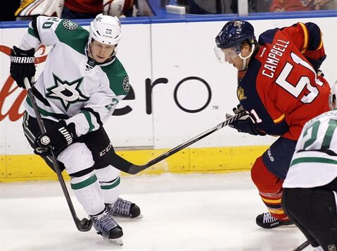 Dallas Stars Antoine Roussel (21) passes the puck as Florida Panthers defenceman Brian Campbell (51) moves in during the third period of an NHL hockey game in Sunrise, Fla., Sunday, April 6, 2014. Roussel and the Stars have agreed to terms on a four-year contract. THE CANADIAN PRESS/AP/Terry Renna