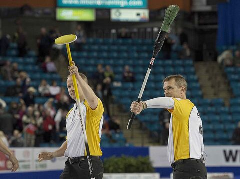 Manitoba skip Jeff Stoughton, right, and lead Mark Nichols wave to the crowd after defeating Quebec at the Tim Hortons Brier in Kamloops, B.C. on Sunday.